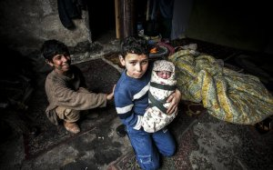 A Syrian refugee boy poses with his newborn brother as their mother lies near them in a house in the Basaksehir district of Istanbul, on March 4, 2014. Syrian government forces are waging a campaign of siege warfare and starvation against civilians as part of its military strategy, a UN-mandated probe said on March 5. Syria's war has since March 2011 killed more than 140,000 people and forced millions more to flee. AFP PHOTO / GURCAN OZTURK
